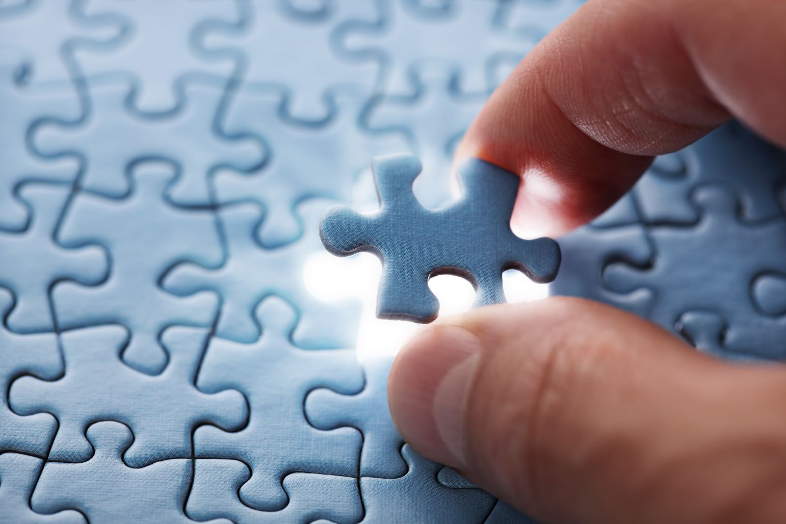 A puzzle piece being added to finish a jigsaw puzzle